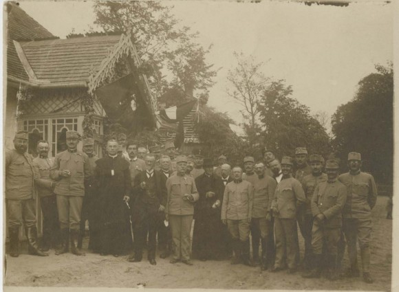 Austrian soldiers and clergy posing in front of a house. (Papers of Loretta Bender)
